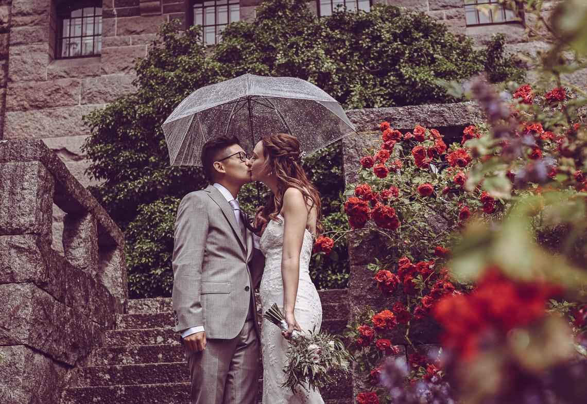 bröllopsporträtt vid Teleborgs slott rosenbuskar brudpar i regn med paraply