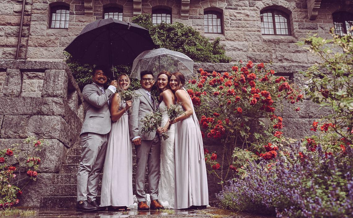 bröllopsporträtt vid Teleborgs slott brudfölje i regn paraply