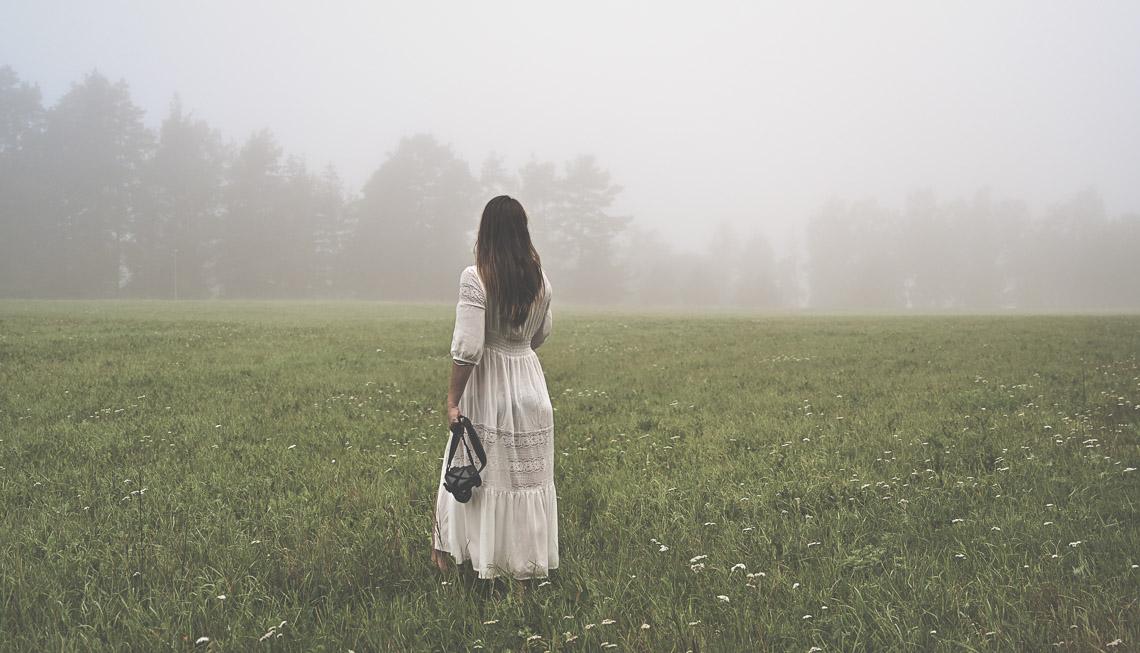 bröllopsfotograf Sandra Hila på en äng vit klänning långt svart hår gräs
