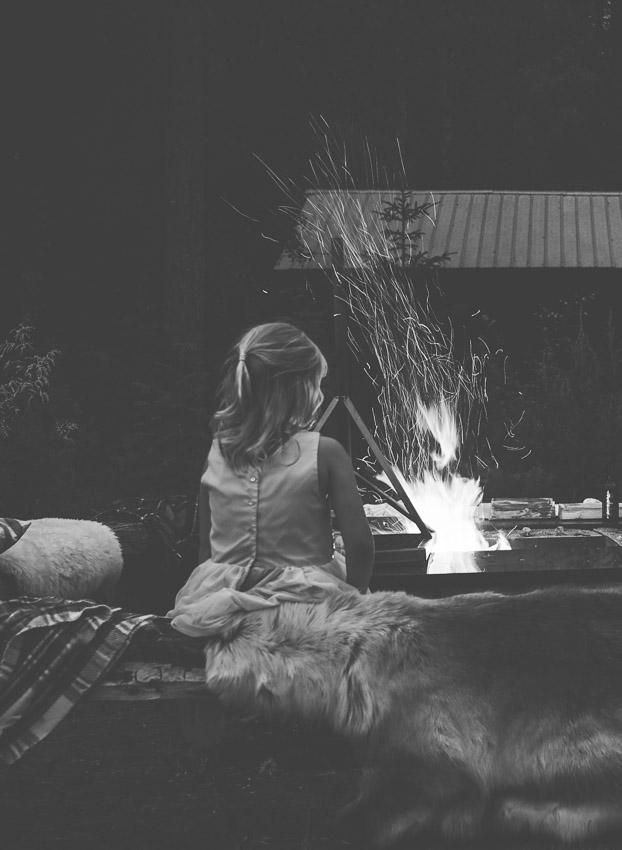 flicka sitter vid elden