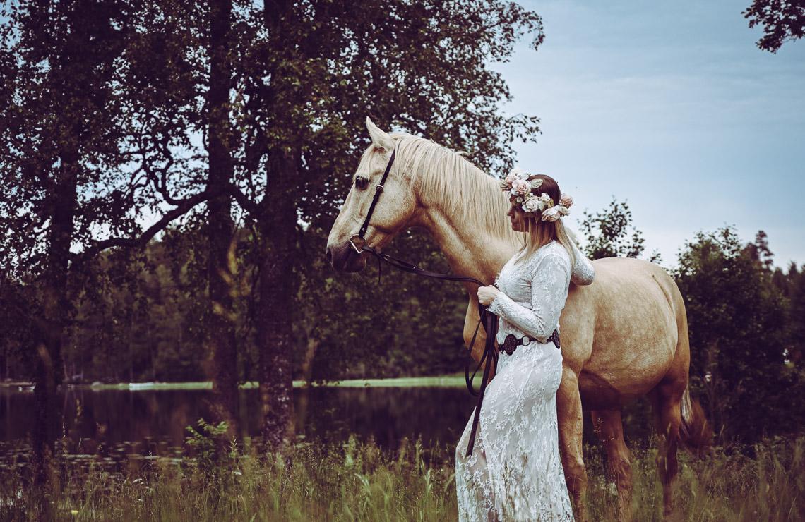 en kvinna med en blomsterkrans leder en häst