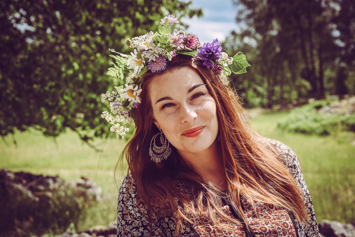 bröllops fotograf Sandra Hila sveriges lantligaste fotografsmåländsk romantik bröllopsfotograf medelålders kvinna med blomsterkrans på midsommar stora örhängen