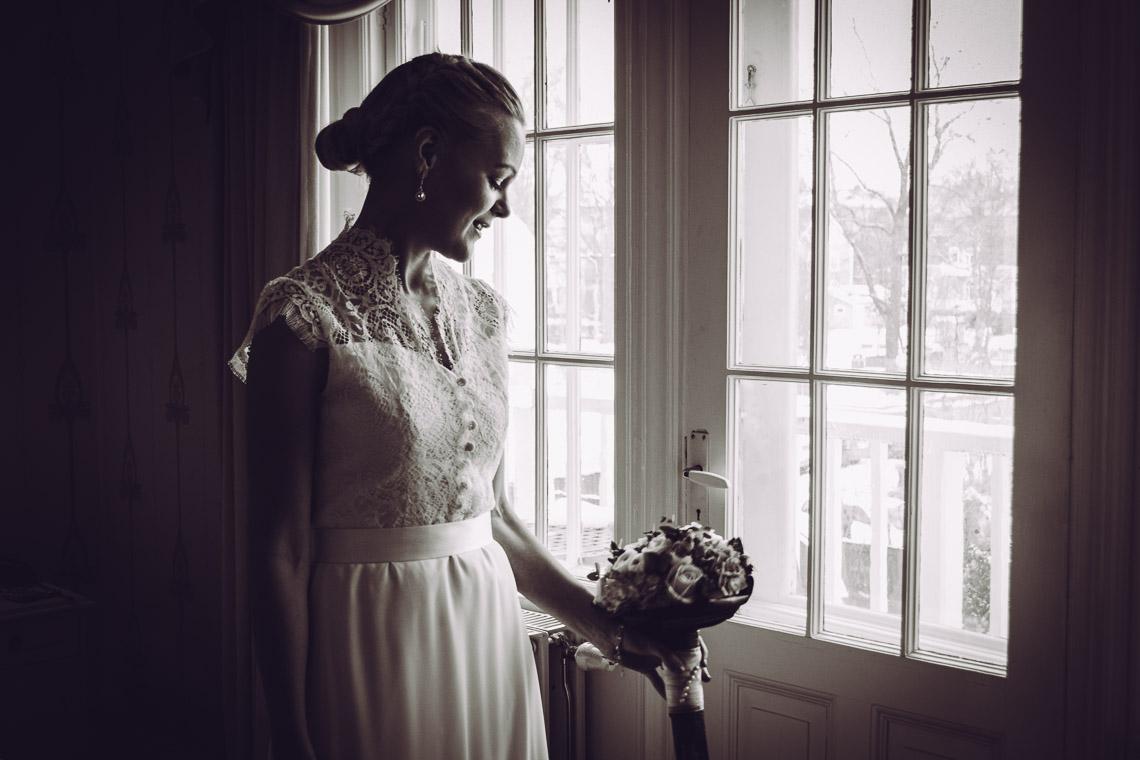 vinterbröllop i Eksjö en brud tittar på sin brudbukett vintage bröllopsbilder